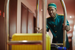 Work of porter. Hall-porter pushing cart with suitcase of new visitor Royalty Free Stock Image