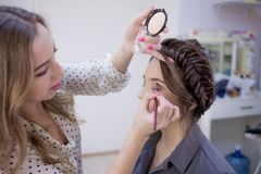 The work of a professional makeup artist. Stylist makeup artist doing makeup and hair in a beauty salon. Professional make-up stock photography