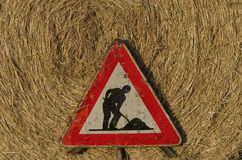 Work in progress roadsign over straw round bale Stock Photo