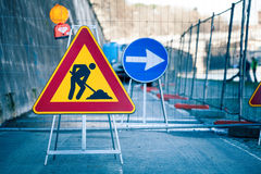 Work in progress. Roadworks, road signs. Men at work. Some signs signage for work in progress on urban street. Barriers and road signs. Silhouette of a worker at Stock Images