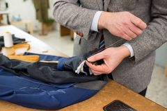 Work in progress with a tailor sewing a jacket. Work in progress with a tailor hand sewing a new blue jacket while standing at a work table in his workshop Stock Photo
