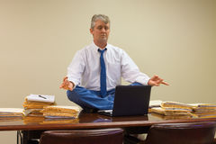 Work related stress relief with yoga as man does pose with stacks of paperwork and computer on conference table Stock Image