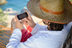 Work & rest: man in hat in a hammock typing on touch phone screen on a summer day Stock Images