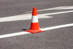 Work on road. Construction cone. Traffic cone, with white and orange stripes on asphalt. Street and traffic signs for signaling. Road maintenance, under Royalty Free Stock Photo