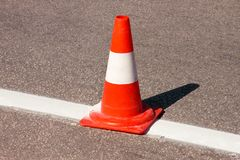 Work on road. Construction cone. Traffic cone, with white and orange stripes on asphalt. Street and traffic signs for signaling. Road maintenance, under stock images