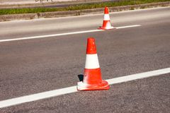 Work on road. Construction cones. Traffic cone, with white and o. Range stripes on asphalt. Street and traffic signs for signaling. Road maintenance, under Royalty Free Stock Photos