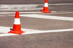 Work on road. Construction cones. Traffic cone, with white and orange stripes on asphalt. Street and traffic signs for signaling. Road maintenance, under Stock Photo
