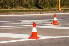 Work on road. Construction cones. Traffic cone, with white and orange stripes on asphalt. Street and traffic signs for signaling. Road maintenance, under Stock Photos