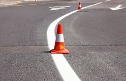 Work on road. Construction cones. Traffic cone, with white and orange stripes on asphalt. Street and traffic signs for signaling. Road maintenance, under Stock Image