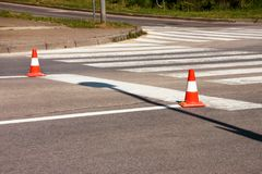Work on road. Construction cones. Traffic cone, with white and orange stripes on asphalt. Street and traffic signs for signaling. Road maintenance, under Royalty Free Stock Photography