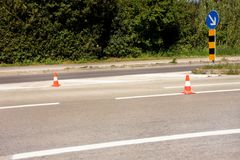 Work on road. Construction cones with traffic sign keep right sign. Traffic cones, with white and orange stripes on asphalt. Traffic signs for signaling and Royalty Free Stock Photo