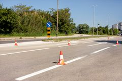 Work on road. Construction cones with traffic sign keep right sign. Traffic cones, with white and orange stripes on asphalt. Traffic signs for signaling and Royalty Free Stock Photos