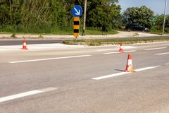 Work on road. Construction cones with traffic sign keep right sign. Traffic cones, with white and orange stripes on asphalt. Traffic signs for signaling and Stock Images