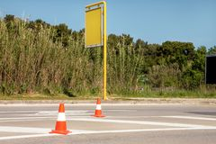 Work on road. Construction cones with yellow advert board at street. Traffic cones, with white and orange stripes on asphalt. Traffic signs for signaling and Stock Image