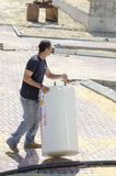 Work Roni Sassi with a solar water heater -Mitzpe Ramon, Israel. Middle East - Mitzpe Ramon, Israel. February 29,The installation of new solar water heaters royalty free stock photo