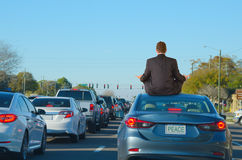 Work Rush Hour Traffic Jam Stress Relief Yoga Humor. A man is dealing with intense work rush hour traffic jam stress by getting relief with doing yoga on top of royalty free stock photography