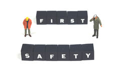 Always work safe. A couple of workmen standing near the words safety first Royalty Free Stock Images