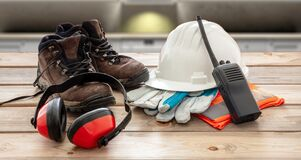 Free Work Safety Protection Equipment. Industrial Protective Gear On Wooden Table, Blur Construction Site Background Royalty Free Stock Photos - 190943988