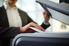 Work of secretary. Secretary making copies or scanning papers on photocopier Royalty Free Stock Images