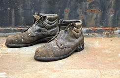 Work shoes. Old worn out work shoes against a brown rusty background royalty free stock image