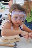 Work shop. A little girl assembling a wood car in a work shop setting Royalty Free Stock Image