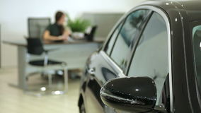 Work in the showroom. Sales Manager at the dealership works at a Desk. In the foreground of the car, the image Manager stock footage
