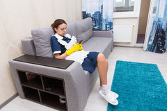 Work shy housekeeper or maid taking a break. Sitting on a comfortable sofa in her uniform and rubber gloves checking her mobile phone Stock Photography