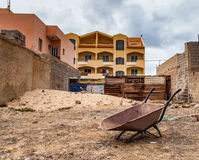 Work site with an older wheelbarrow. A small, empty construction site in a suburb with an older wheelbarrow, pile of sand, walls and a newly constructed house on Royalty Free Stock Images