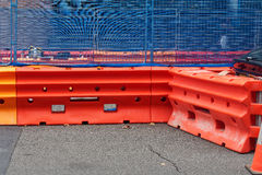 Work Site Safety Barriers. A work site enclosed by bright orange water filled barriers and a blue mesh covered wire fence royalty free stock photos