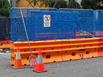 Work Site Safety Barriers. A work site enclosed by bright orange water filled barriers and a blue mesh covered wire fence royalty free stock photography