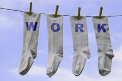 Work socks. Four white socks pegged on a clothes line with the words Work on them Stock Images