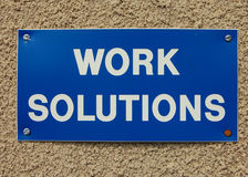 Work solutions. Written in white on a blue sign with a grungy background Royalty Free Stock Photos