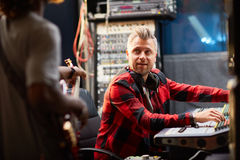 Work of sound operator. Sound operator looking at musician during recording Royalty Free Stock Photo