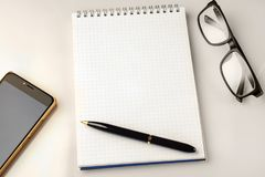 Work space accessories: pen, notebook, glasses and a modern smartphone Royalty Free Stock Image