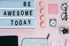 Work Space Be Awesome Today On Pink Glasses Notepad Kicking Pencils Plant Macaroons Alarm Clock Top View Stock Photos