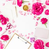 Work space with clipboard, notebook, accessories and pink flowers on white background. Flat lay, top view. Work space with clipboard, notebook, accessories and royalty free stock photography