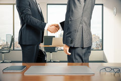 Work space with laptop and businessmen shaking hands in modern o Royalty Free Stock Image