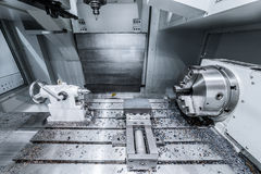 Work space of modern CNC milling machine. Working area of modern double-spindle CNC metalworking machine. Tinted in cold industrial colors Stock Photo