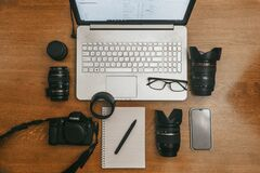 Free Work Space Photographer With Laptop, Digital Camera, Lenses, Notebook, Glasses, Pen, Phone And Camera Accessory. View On Dark Wood Stock Image - 176886801