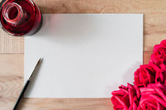Work space watercolor paper or note paper with black ink, brush and Bouquet of roses on wooden table. Royalty Free Stock Photos
