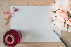 Work space watercolor paper or note paper with red ink,colorful clips,stationery, brush and Bouquet of pink roses on wooden table. Suitable for special stock photo