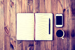 Work space. White cell phone, pen, cup of coffee and notebook on wooden table. Work space. Instagram vintage picture Royalty Free Stock Photo