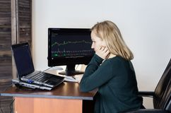 Work on a stock exchange. Businesswoman watching changes in the currency exchange chart royalty free stock photo
