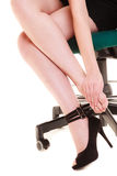 Work stoppage. Tired businesswoman massaging feet. Work stoppage and leg pain. Closeup of tired businesswoman woman sitting on chair and massaging feet isolated Stock Image