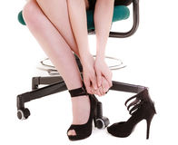 Work stoppage. Tired businesswoman taking shoes off. Work stoppage and leg pain. Closeup of tired businesswoman woman sitting on chair and taking shoes off Royalty Free Stock Photo