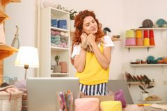 Amicable woman wearing yellow shirt working in art studio. Work in studio. Amicable young red-haired woman wearing stylish bright yellow shirt working in stock images