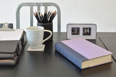 Work table with book,pencils, cup of coffee and clock Stock Photography