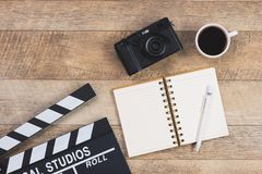 Work table of producer. Movie clapper, camera and coffee cup, on stock photos