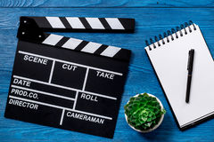 Work table of producer. Movie clapperboard and notebook on blue wooden table background top view Royalty Free Stock Image
