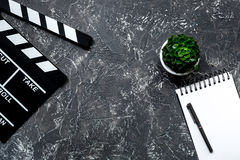Work table of producer. Movie clapperboard and notebook on grey stone background top view copyspace Royalty Free Stock Photo